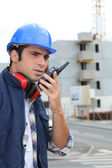 Foreman on construction site giving orders via radio — Stock Photo