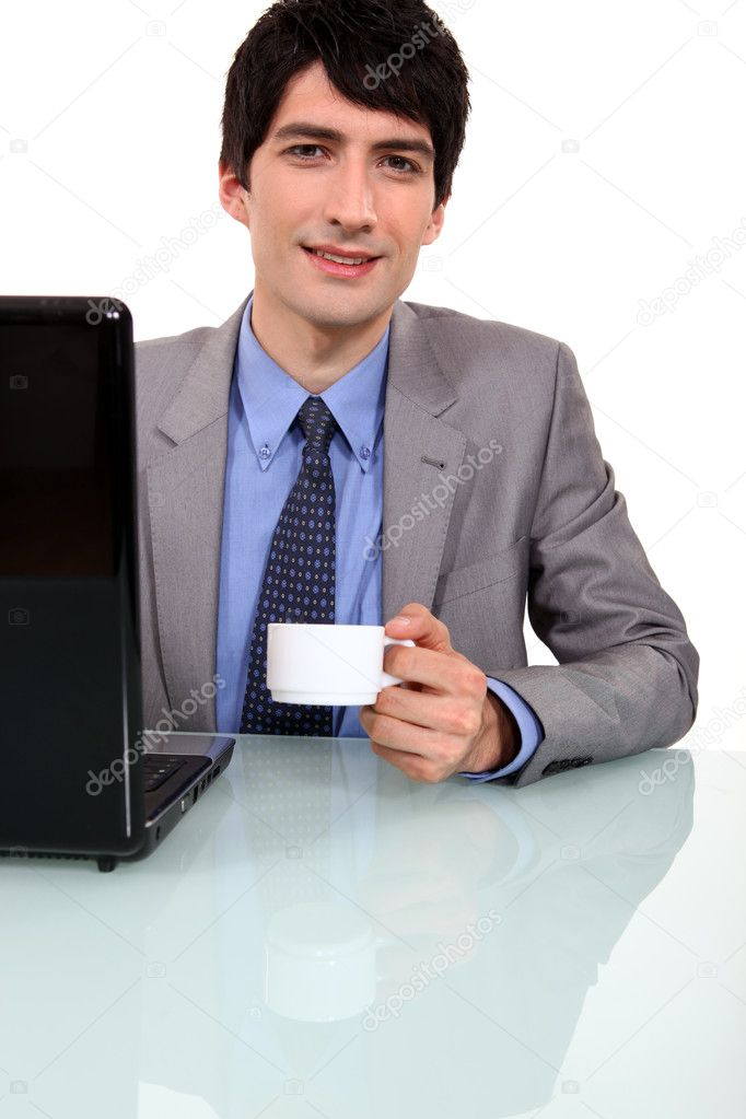 Worker drinking coffee in front of laptop — Stock Photo #10194053