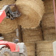 Tractor lifting bail of hay — Stock Photo