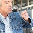 Man drinking wine in a cellar - Stock Photo