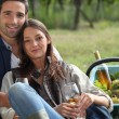 Couple with basket of grapes and wine — Stock Photo #10278254