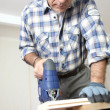 Man piercing a hole through a wooden plank — Stock Photo #10280635