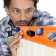 Carpenter using a spirit level - Stock Photo
