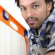 Man using spirit-level to check cabinet door - Stock Photo