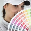 Foto Stock: Female decorator choosing color from swatch