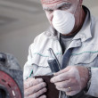 Man wearing mask whilst sanding — Stock Photo
