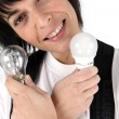 Portrait of woman holding two light bulbs — Stock Photo
