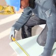 Stock Photo: Worker measuring plasterboard