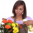Florist spraying a bunch of flowers with water — Stock Photo
