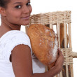 Stock Photo: Young black womholding bread in her arms