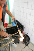 Plumber heating up copper pipe — Stock Photo