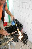 Fontanero calentar el tubo de cobre — Foto de Stock