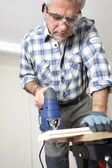 Man piercing a hole through a wooden plank — Stock Photo