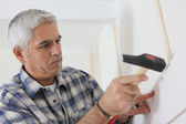 Grey-haired man repairing house — Stock Photo