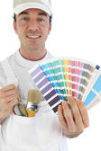 Smiling painter showing swatches — Stock Photo