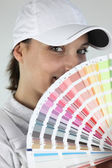 Female decorator choosing color from swatch — Stock Photo