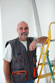 Bald handyman posing by ladder — Stock Photo