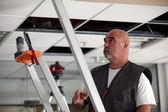 偽の天井の上に置くことの労働者 — ストック写真