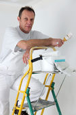 Painter posing by his ladder — Stock Photo