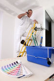Painter at work on ladder making a call — Stock Photo