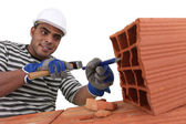 Bricklayer at work with red bricks indoors — Stock Photo