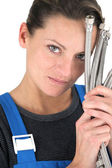 Female plumber with handful of pipes — Stock Photo