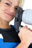Closeup portrait of young blonde female apprentice holding spot welder — Stock Photo