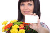 Florist with a bunch of flowers and a business card left blank for your message — Stock Photo