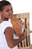 Young black woman holding bread in her arms — Stock Photo