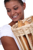 Woman holding basket of bread — Stock Photo