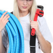 Tradeswoman holding corrugated tubing and a pipe wrench — Stock Photo