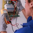 Stock Photo: Female electriciwith voltmeter