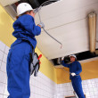 Stock Photo: Two electrician repairing ceiling lighting