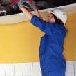 Plumber running pipes across a ceiling — Stock Photo #10322192