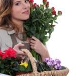 Beautiful florist holding flowers — Stock Photo