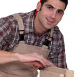 Woodworker finishing a window frame - Stock Photo