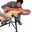 Stock Photo: Carpenter leveling plank
