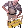 A carpenter making a wooden frame - Stock Photo