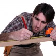 Man measuring wooden frame - Stock Photo