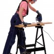 Woman carpenter using a jigsaw. - Stock fotografie