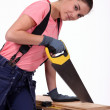 Royalty-Free Stock Photo: Young woman sawing a wooden board