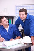 Two factory workers in the office checking stock — Stock Photo