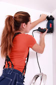 Female drilling ceiling — Stock Photo