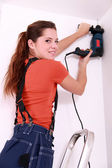 Woman drilling roof — Stock Photo