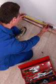 Plumber measuring length of copper pipe — Stock Photo
