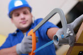 Plumbing sawing plastic pipe — Stock Photo
