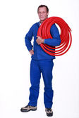 Tradesman holding coiled tubing around his shoulder — Stock Photo