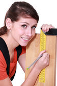 Female carpenter marking out wood with set-square — Stock Photo