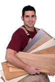 Carpenter carrying plywood — Stock Photo