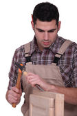 Carpenter with a hammer and a chisel — Stock Photo